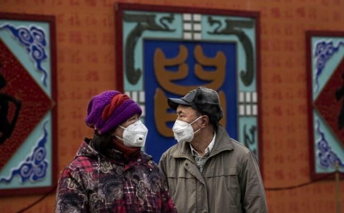 Китайская пара в защитных масках во время празднования китайского Нового года, Пекин, Китай, 26 января 2020 года. Kevin Frayer/Getty Images   Epoch Times Россия