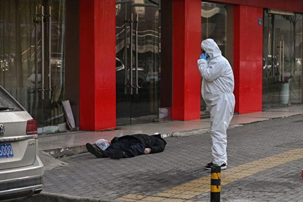 Человек в защитном костюме стоит возле старика, который скончался на улице возле больницы в Ухане, 30 января 2020 года. HECTOR RETAMAL/AFP via Getty Images | Epoch Times Россия
