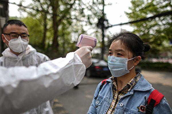 Мужчина в защитной одежде проверяет температуру женщины рядом с жилым районом в Ухане, Хубэй, 7 апреля 2020 года. HECTOR RETAMAL/AFP via Getty Images | Epoch Times Россия
