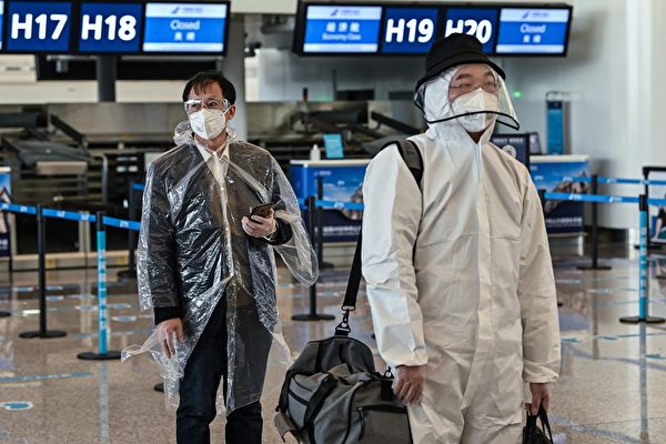 Пассажиры в защитной одежде в аэропорту Тяньхэ, Ухань, Китай, 8 апреля 2020 года. HECTOR RETAMAL/AFP via Getty Images | Epoch Times Россия