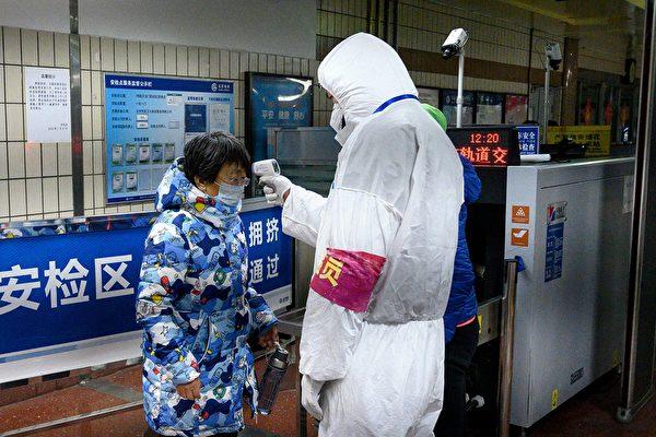 Сотрудники службы безопасности в защитной одежде проверяют температуру пассажиров у входа на станцию метро в Пекине, 28 января 2020 года. NOEL CELIS/AFP via Getty Images | Epoch Times Россия
