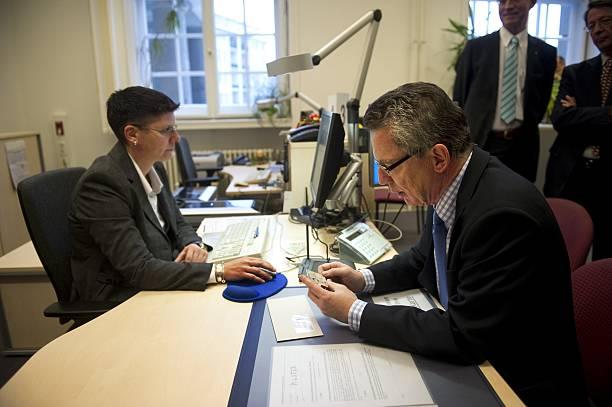 Министр внутренних дел Германии Томас де Мезьер (справа) проверяет свое новое биометрическое удостоверение. Фото: ODD ANDERSEN/AFP via Getty Images | Epoch Times Россия