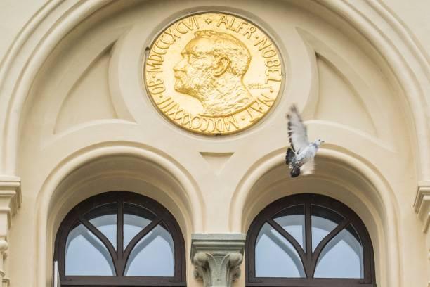 Голубь мира пролетает мимо рельефа Альфреда Нобеля после того, как он был выпущен перед Нобелевским центром мира в Осло, Норвегия. Фото:  ALI ZARE/NTB/AFP via Getty Images | Epoch Times Россия