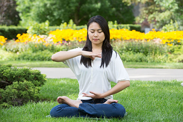Девушка выполняет одно из упражнений Фалунь Дафа. Фото The Epoch Times | Epoch Times Россия