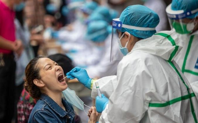 Медицинский работник берёт образец у жителя Уханя для тестирования на COVID-19, Китай, 15 мая 2020 года. STR / AFP через Getty Images | Epoch Times Россия