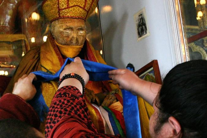 Верующие украшают нетленное тело Даши-Доржо Итигэлова, сибирского буддийского ламы. Улан-Удэ, столица Республики Бурятия. Фото: HO/AFP/Getty Images   Epoch Times Россия