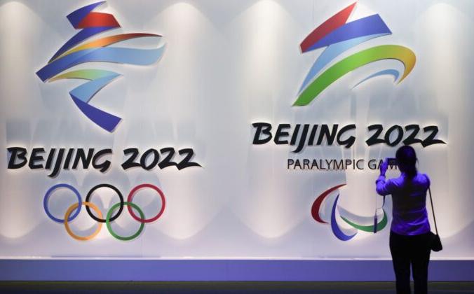 Посетитель фотографирует логотипы предстоящих зимних Олимпийских и Паралимпийских игр в Пекине 2022 года на Пекинской олимпийской выставке, 8 августа 2018 года. WANG ZHAO/AFP via Getty Images | Epoch Times Россия