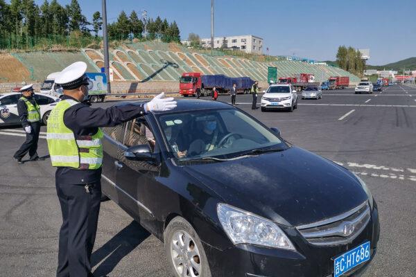 Сотрудник полиции направляет водителя автомобиля для регистрации информации на съезде с шоссе в Цзилине, Китай, 13 мая 2020 года. STR/AFP via Getty Images | Epoch Times Россия