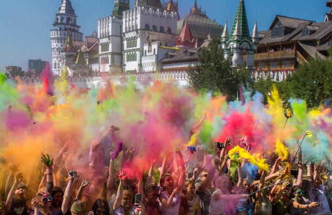 26 июля: Люди бросают цветной порошок на Фестивале красок в Москве. Изначально так отмечали праздник Холи в Северной Индии, бросая друг на друга яркие краски, люди встречали весну и отгоняли злых духов. Фото: ALEXANDER UTKIN/AFP/Getty Images | Epoch Times Россия