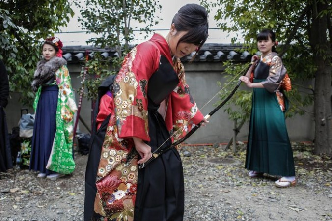Участница натягивает тетиву лука во время мероприятия по стрельбе  из лука на церемонии совершеннолетия в храме Сандзюсангэндо, Киото, Япония, 17 января,2016. Фото: Taro Karibe/Getty Images   Epoch Times Россия