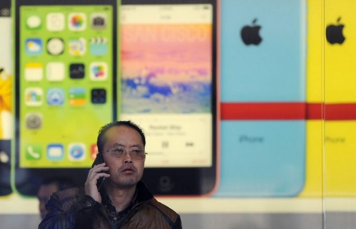 Китаец звонит по мобильному телефону в магазине Apple в Пекине 17 января 2014 года.  Фото: WANG ZHAO/AFP/Getty Images | Epoch Times Россия
