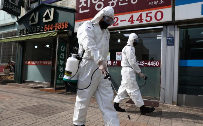 Южнокорейские солдаты, одетые в защитное снаряжение, распыляют антисептический раствор для защиты от коронавируса вдоль улицы в районе Каннам в Сеуле, Южная Корея, 9 марта 2020 года . Chung Sung-Jun / Getty Images | Epoch Times Россия
