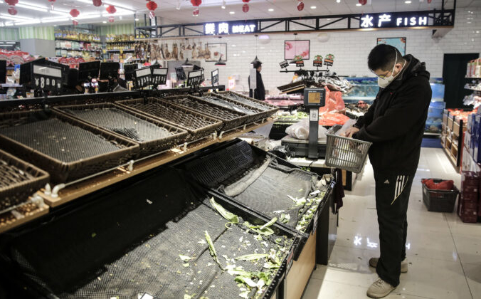 Посетители  в защитных масках перед пустыми овощными прилавкам на рынке в Ухане, провинция Хубэй, Китай, 23 января 2020г. Getty Images   Epoch Times Россия