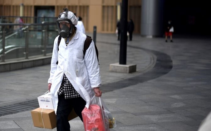 Мужчина в маске несёт вещи, которые он купил в супермаркете Уханя, Китай, 30 марта 2020 года. Ноэль Селис/AFP через Getty Images | Epoch Times Россия