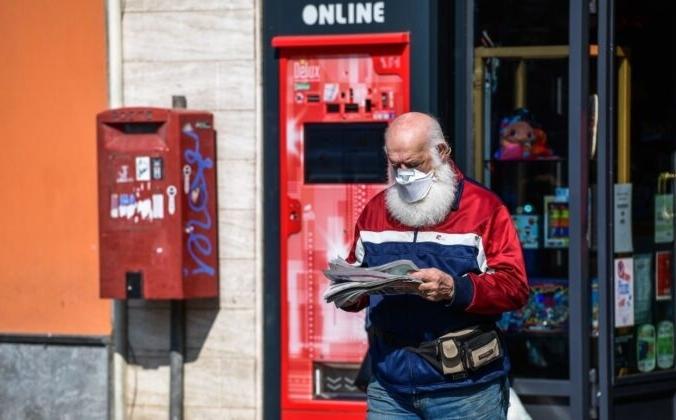 Житель города Тревиоло, Италия, 9 апреля 2020 года выходит из магазина с купленной газетой. Miguel Medina/AFP via Getty Images   Epoch Times Россия