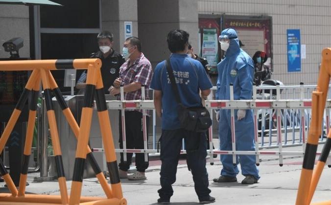 Сотрудник службы безопасности в защитном костюме стоит на страже в жилом районе, находящемся в режиме изоляции, недалеко от восточного рынка Юйцюань в Пекине, Китай, 15 июня 2020 года. NOEL CELIS/AFP via Getty Images | Epoch Times Россия