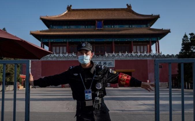 Охранник в маске закрывает ворота с внешней стороны Запретного города в Пекине (на заднем плане) из-за COVID-19, 12 апреля 2020 года. Nicolas Asfouri/AFP via Getty Images | Epoch Times Россия