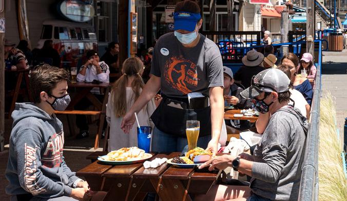 Посетители в масках сидят на открытом патио ресторана в Сан-Франциско. David Paul Morris/Bloomberg via Getty Images | Epoch Times Россия