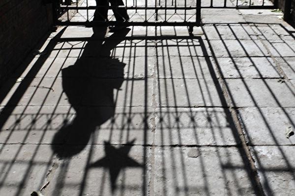Тень женщины, проходящей мимо металлических ворот, украшенных эмблемой коммунистической звезды, в старом жилом комплексе Пекина 15 ноября 2008 года. FREDERIC J. BROWN/AFP/Getty Images | Epoch Times Россия