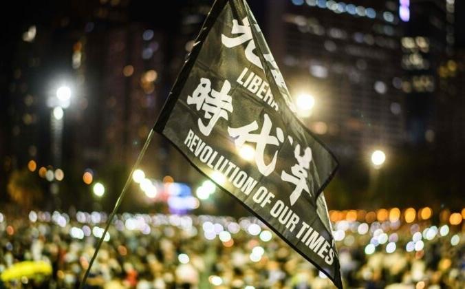 Участники митинга поднимают флаг с надписью «Освободите Гонконг, революция нашего времени» во время акции при свечах в парке Виктория в Гонконге 4 июня 2020 года. ANTHONY WALLACE/AFP via Getty Images   Epoch Times Россия