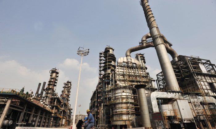 Рабочий едет на велосипеде на нефтеперерабатывающем заводе китайской Sinopec в Ухане, провинция Хубэй в центральном Китае, 10 мая 2011 г. (STR / AFP / Getty Images) | Epoch Times Россия