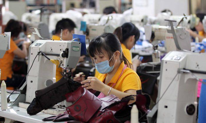 Обувная фабрика в Цзиньцзяне, провинция Фуцзянь на юге Китая, 17 сентября 2013 г. (STR / AFP / Getty Images)   Epoch Times Россия