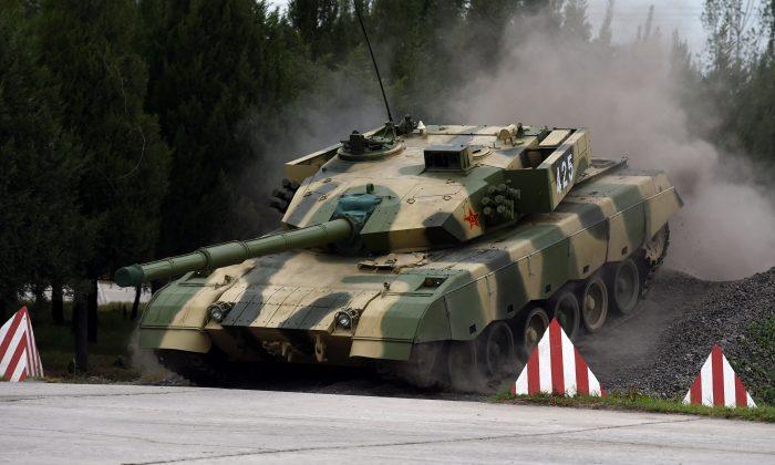 Один из современных китайских танков пересекает препятствие во время демонстрации вождения в Инженерной академии бронетанковых сил Народно-освободительной армии в Пекине 22 июля 2014 г. (Greg Baker / AFP / Getty Images) | Epoch Times Россия