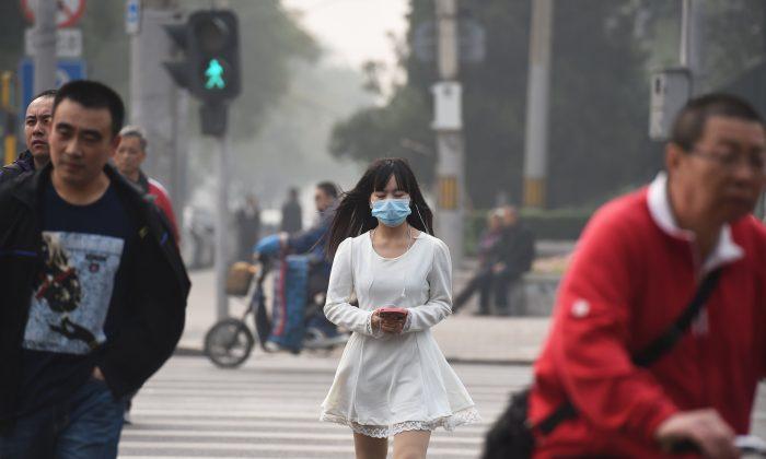 Женщина в маске в грязный день в Пекине 20 октября 2014 года. Пекин вернулся к нормальной жизни после закрытия заседаний АТЭС 12 ноября 2014 года, когда задержанных петиционеров освободили, подали тепло, возобновили работу завода и автомобиль были сняты ограничения и так далее. (Грег Бейкер / AFP / Getty Images) | Epoch Times Россия