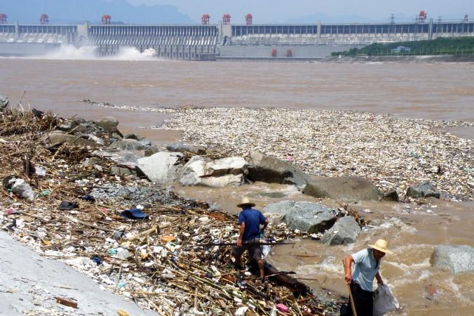 Двое рабочих убирают мусор вдоль берега реки Янцзы вблизи дамбы Трёх ущелий в Ичане, провинция Хубэй, 1 августа 2010 г. Фото: STR/AFP/Getty Images | Epoch Times Россия