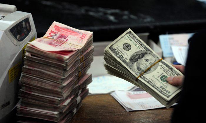 Сотрудник китайского банка пересчитывает пачку долларов США вместе со стопками банкнот 100 китайских юаней в банке в Хэфэе, провинция Аньхой, 9 марта 2010 г. (STR / AFP / Getty Images)   Epoch Times Россия