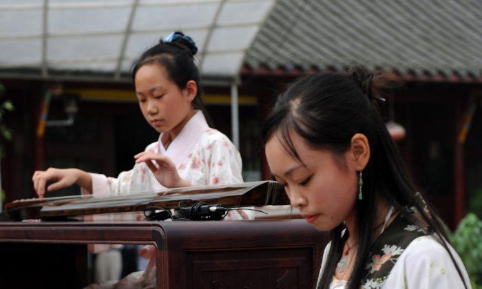 Молодые китаянки играют на классической и сложной гуцинь, родственнице семейства цитр. (China Photos / Getty Images) | Epoch Times Россия