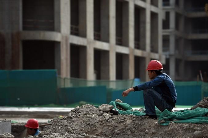 Строитель отдыхает возле здания в новом финансовом районе города Тяньцзинь на севере Китая, 14 мая 2015 года. Один масштабный правительственный проект включает десятки небоскребов. Он рассматривается как будущий «китайский Манхэттен». Но замедление темпов роста экономики увеличило сомнения в жизнеспособности таких проектов, учитывая увеличение числа «городов-призраков» в стране. Фото: Greg Baker/AFP/Getty Images | Epoch Times Россия