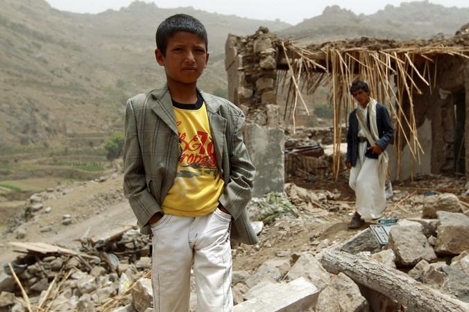 Йеменский мальчик стоит у своего разрушенного авиаударами дома в деревне Бани Матар, расположенной в 70 км от Саны, Йемен, 4 апреля, 2015 год.Фото: MOHAMMED HUWAIS/AFP/Getty Images   Epoch Times Россия