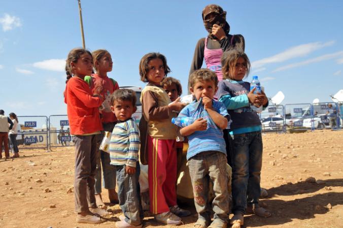 Сирийские курды спасаются от боевиков «Исламского государства», пересекая границу с Турцией. Фото: Stringer/Getty Images | Epoch Times Россия