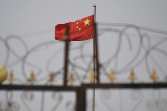 Китайский флаг за колючей проволокой на жилом комплексе в уезде Янгисаре, к югу от Кашгара, Синьцзян-Уйгурский автономный район, 4 июня 2019 года. Greg Baker/AFP via Getty Images   Epoch Times Россия
