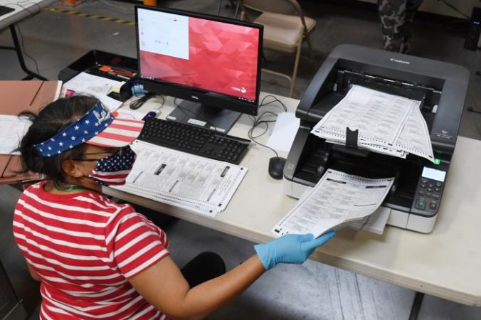 Работник избирательной комиссии округа Кларк сканирует бюллетени, отправленные по почте, в Северном Лас-Вегасе, штат Невада, 20 октября 2020 года. Ethan Miller/Getty Images | Epoch Times Россия