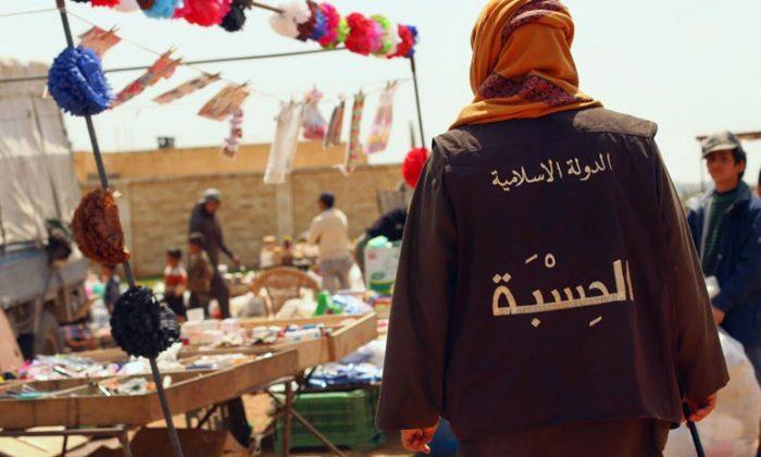 Член вице-полиции группы Исламского государства, известный как «Хисба», патрулирует рынок в городе Ракка, Сирия. Арабские слова на жилете гласили: «Исламское государство - Хисба (вице-полиция)». 17 апреля 2015 года (Сайт боевиков через AP) | Epoch Times Россия