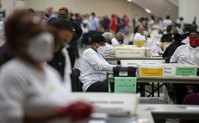 Роботник избирательного департамента Детройта помогает обрабатывать бюллетени для заочного голосования в Кобо-центр, Детройт, штат Мичиган, 4 ноября 2020 года. Elaine Cromie/Getty Images | Epoch Times Россия