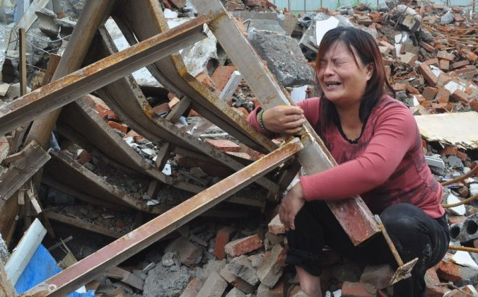 Жена Чжан Хунвэя стоит на коленях среди обломков своего дома и плачет в городе Синьчжэн провинции Хэнань в центральном Китае, 8 августа 2014 года. Чжан и его жена были похищены группой анонимных мужчин, которые ворвались в них во время сна. Когда пару часов спустя отпустили, они обнаружили, что их дом был снесен. (Скриншот / 163.com) | Epoch Times Россия