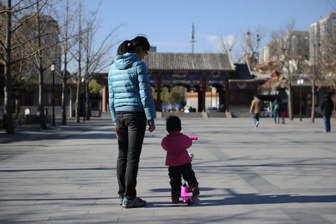 Женщина и ребёнок гуляют в парке в Пекине 26 ноября 2013 года. Китайские власти проводят «политику одного ребёнка» с 1979 года. Фото: Wang Zhao/AFP/Getty Images | Epoch Times Россия