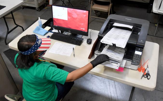 Работник избирательной комиссии сканирует бюллетени для голосования в округе Кларк, Северный Лас-Вегас, штат Невада, 7 ноября 2020 года. Ethan Miller/Getty Images | Epoch Times Россия