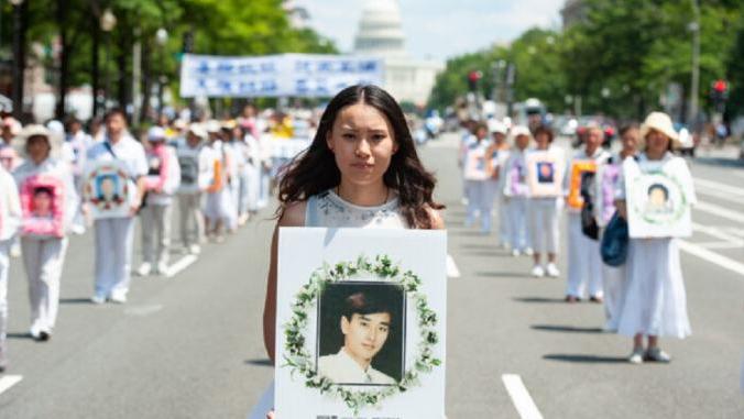 Участница шествия держит фотографию мужчины, убитого из-за преследования Фалуньгун коммунистическим режимом КНР, Вашингтон, 17 июля 2014 года. Larry Dye/The Epoch Times   Epoch Times Россия