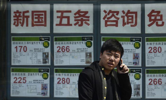 Китаец разговаривает по мобильному телефону перед агентством недвижимости в Пекине 15 апреля 2013 г. (Ван Чжао / AFP / Getty Images) | Epoch Times Россия