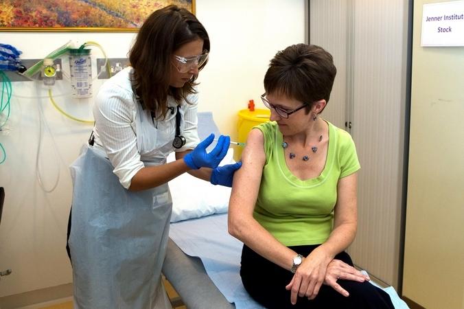 Научный сотрудник Оксфордского университета доктор Фелисити Хартнелл впрыскивает  вакцину против лихорадки Эбола типа ChAd3 первому здоровому добровольцу Великобритании Рут Аткинс, Оксфорд, Англия, 17 сентября, 2014 год. Фото: Steve Parsons-WPA Pool/Getty Images | Epoch Times Россия