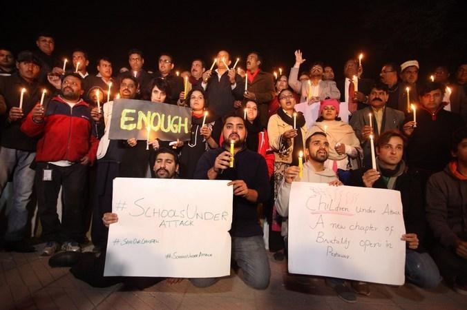 Члены пакистанского гражданского общества и журналистов зажгли свечи в память о жертвах нападения боевиков Талибана на школу в Пешаваре, Пакистан, 16 декабря, 2014 год. Фото:  M SHAHID/AFP/Getty Images   Epoch Times Россия