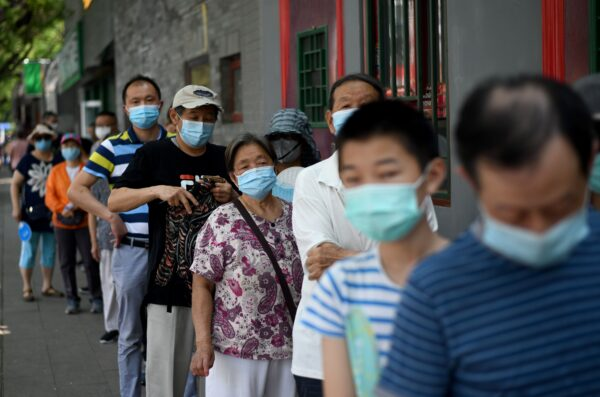 Люди выстраиваются в очередь, чтобы сдать мазок во время массового тестирования на коронавирус COVID-19 в Пекин (Китай) 21 июня 2020 года. NOEL CELIS/AFP via Getty Images | Epoch Times Россия