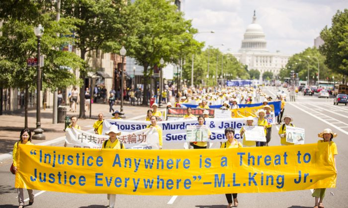 Последователи Фалуньгун маршируют на параде, призывая к прекращению преследования в Китае, на фоне здания Капитолия США в Вашингтоне, округ Колумбия, 17 июля 2014 г. (Эдвард Дай / Epoch Times)   Epoch Times Россия