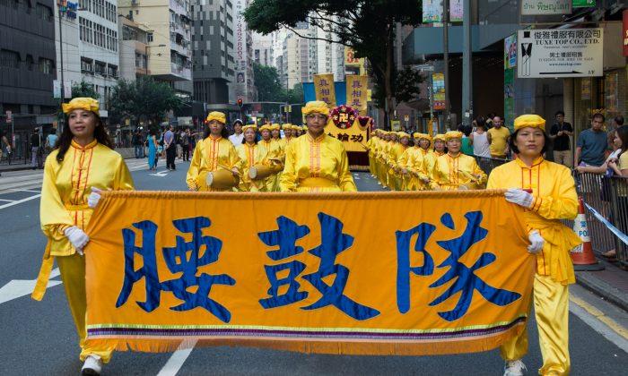 Последователи Фалуньгун вместе с людьми из глобального центра по выходу из Китайской партии маршируют на параде по улицам Гонконга в знак протеста против Национального дня Китая 1 октября 2014 г. (Бенджамин Честин / Epoch Times) | Epoch Times Россия