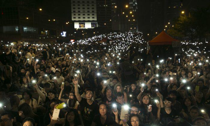 Десятки тысяч продемократически настроенных держат фонарики во время выступлений 4 октября 2014 года в Гонконге. На 10 октября должны начаться переговоры между студентами, протестующими за всеобщее избирательное право, и правительством Гонконга. (Паула Бронштейн / Getty Images)   Epoch Times Россия