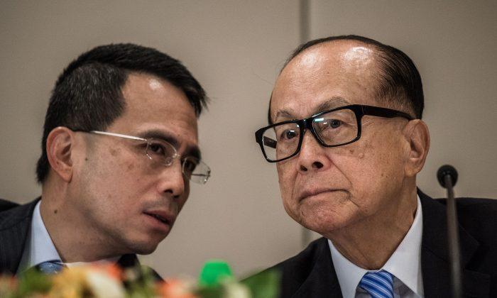 Гонконгский магнат Ли Кашинг (справа) слушает своего сына Виктора Ли Цар-куоя во время пресс-конференции в Гонконге 9 января 2015 года. По словам демократического активиста Эдварда Чина, самый богатый человек Азии испытывает давление со стороны Пекина. . (Филипп Лопес / AFP / Getty Images)   Epoch Times Россия